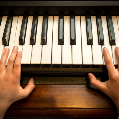Closeup photo of child's hands playing on the piano
